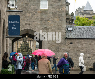 Holyrood, Edinburgh, Scotland, United Kingdom, 12th August 2018. UK Weather: the rain and mist as the remnants of Storm Debby hits the capital does not deter tourists at Holyrood Palace. People queuing to enter the palace holding umbrellas - Stock Image
