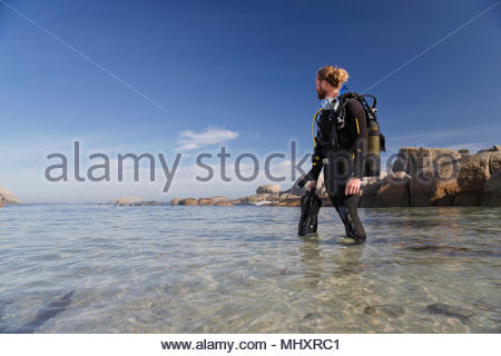 Man in wetsuit going ocean scuba diving from beach - Stock Image