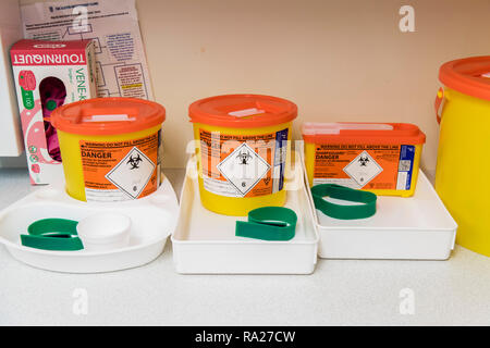 Trays set up for taking blood samples including sharps boxes, tourniquets and cotton balls. - Stock Image