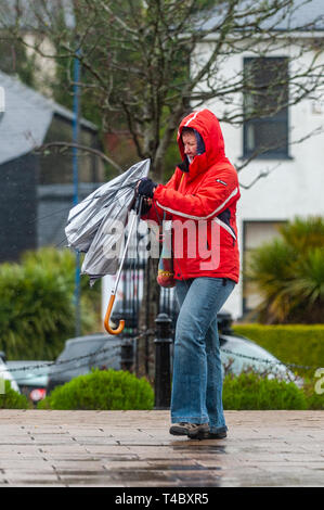 Bantry, West Cork, Ireland. 15th Apr, 2019. Much of Ireland is currently in the midst of a Status Orange Rainfall Warning and a Status Yellow Wind Warning, issued by Met Éireann. The wind is blowing gale force in Bantry where this woman struggled with her umbrella. Credit: Andy Gibson/Alamy Live News. - Stock Image