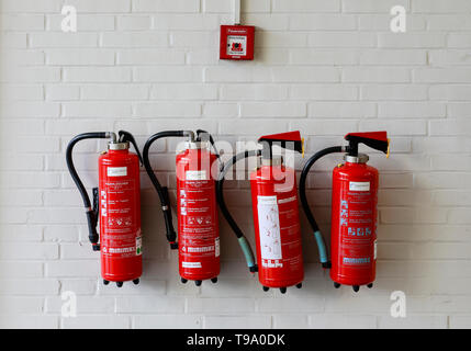 31.03.2019, Hannover, Lower Saxony, Germany - Four red fire extinguishers on a wall under a fire alarm at the Hannover Fair. 00X190331D039CAROEX.JPG [ - Stock Image
