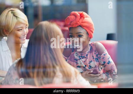 Young women friends talking in cafe - Stock Image
