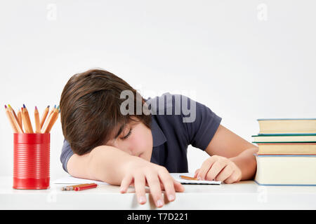 Tired and overworked caucasian teenager pupil felt asleep at the desk while doing his homework. Concept of hard educational process - Stock Image