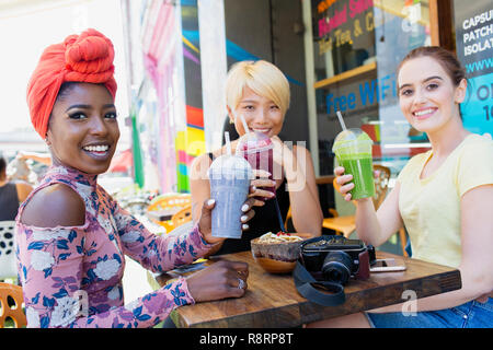 Portrait smiling young women friends drinking smoothies at sidewalk cafe - Stock Image