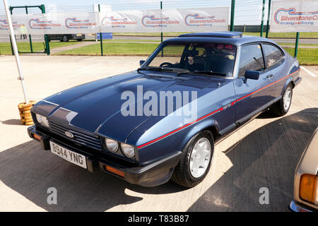 Three-quarters front  view of a Blue, 1984, Ford Capri , part of the 50th Anniversary celebrations at the 2019 Silverstone Classic Media Day - Stock Image