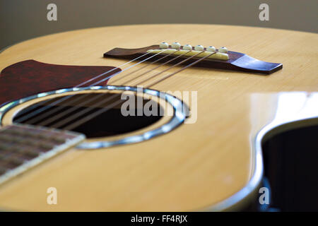Looking  over the sound hole and strings of an electric acoustic guitar. - Stock Image