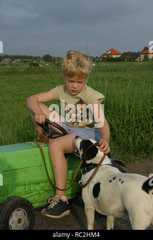 Boyish girl on plastic pedal tractor in countryside in summer with dog - Stock Image