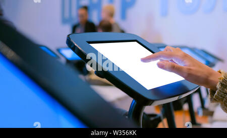 Woman using interactive touchscreen kiosk with white empty screen - Stock Image