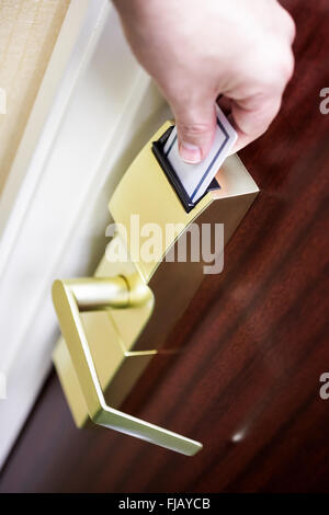 Person's hand unlocking a hotel room door by inserting a key card into an electronic door lock. - Stock Image