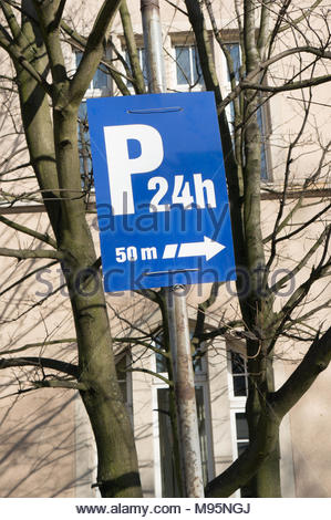 Blue sign showing direction to a 24h parking area - Stock Image