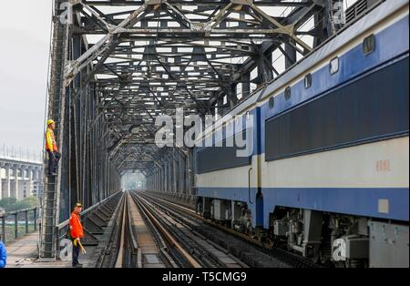 (190423) -- CHONGQING, April 23, 2019 (Xinhua) -- Workers wait for an electrical locomotive to pass on the previous Baishatuo Yangtze River railway bridge in Jiangjin of southwest China's Chongqing Municipality, April 23, 2019. The previous Baishatuo Yangtze River railway bridge, completed in 1959, will stop service after April 24. All trains will run on the new double decker steel truss cable stay railway bridge after that day. The new bridge has 4 tracks on the upper deck for passenger trains with a designed speed of 200 kilometers per hour and 2 tracks on the lower deck for cargo trains wit - Stock Image