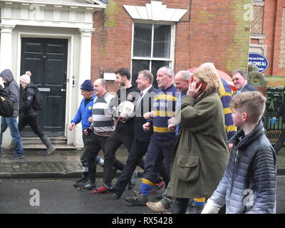 Ashbourne Shrovetide Football 2019. Local firefighter Paul Holmes is escorted through the town to turn up the ball for the Ash Wednesday Game. - Stock Image