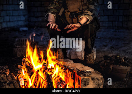 Special forces soldier warming his hands over a fire in a ruined building. - Stock Image