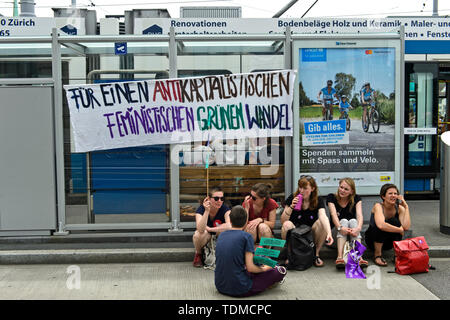 Protesting women sitting unter a banner calling for the Anticapitalist, feminin, ecological change, display at the women's strike 14 June 2019, Zurich - Stock Image