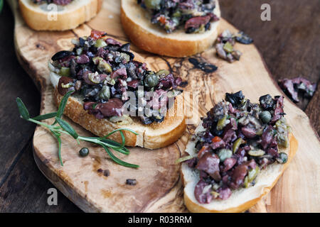 Homemade mixed Olive Tapenade made with garlic, capers, olive oil, Kalamata, black and green olives spread over toasted bread. Extreme shallow depth o - Stock Image
