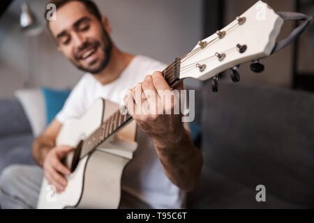 Photo of handsome man 30s wearing casual t-shirt playing acoustic guitar while sitting on sofa in apartment - Stock Image
