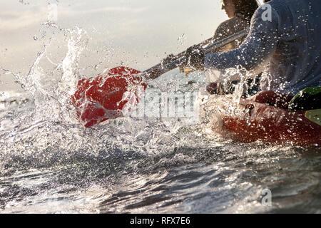 Closeup photo of splashes from kayak or canoe paddle at sea bay. Kayaking or canoeing concept - Stock Image