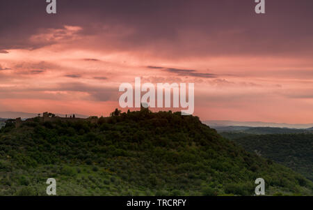Medieval walls and towers of the town of Monticchiello in Tuscany Italy during a rainstorm at sunset - Stock Image