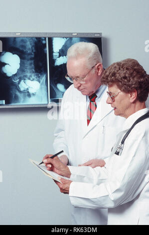 Doctor and Nurse Discuss a Patient's Progress, USA - Stock Image