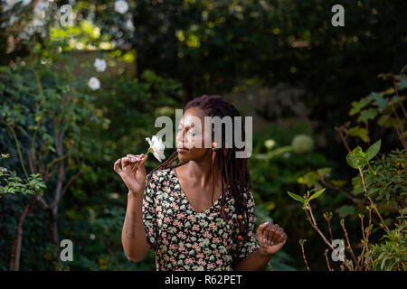 An African woman smelling a rose in a garden - Stock Image