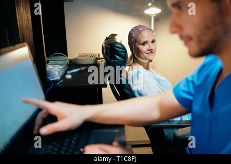 Doctor Doing Brain Medical Exam On Old Woman In Hospital - Stock Image