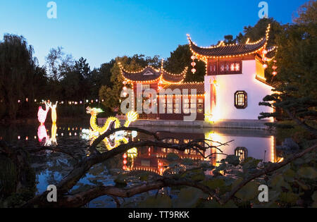 The Stone Boat pavilion and Lotus pond with the Magic of Lanterns exhibit at dusk in the Chinese Garden, Montreal Botanical Garden, Quebec, Canada - Stock Image