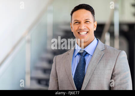 cheerful businessman standing by stairway - Stock Image