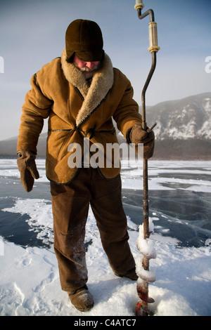 Russia, Siberia, Baikal; Undergoing preparations for fishing on frozen lake baikal in winter - Stock Image