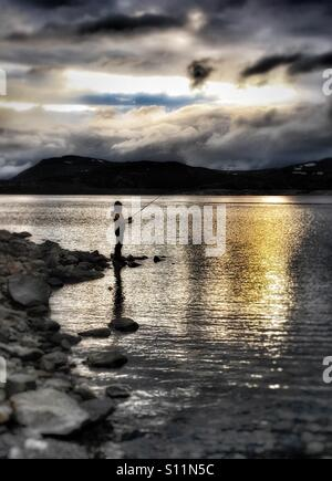 Evening fishing trip with the weather closing in - Stock Image