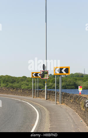 Sharp left hand bend marked with chevron signs on a severe curve on the A673 as it runs past lower Rivington reservoir - Stock Image