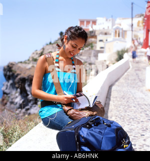Young female tourist looking at a guide book listening on ipod in Santorini Greek Islands Greece  KATHY DEWITT - Stock Image