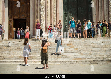 Tourists ouside of Duomo di Siena (Siena Cathedral), Tuscany, Italy - Stock Image