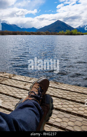 Hiker relaxing on a boardwalk by a lake - Stock Image