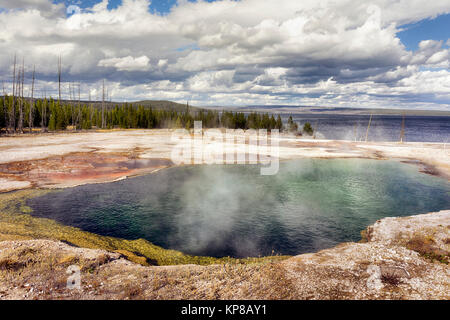 Thermal pool with Yellowstone Lake in background. Yellowstone National Park, Wyoming, USA - Stock Image
