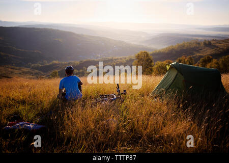 Rear view of man sitting by tent on grassy field against sky - Stock Image