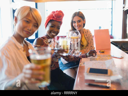Portrait smiling, confident young women friends toasting cocktails in bar - Stock Image