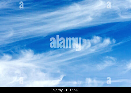 High level white cirrus clouds distorted by strong high level winds. - Stock Image