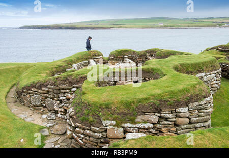 Tourists at Skara Brae, a stone-built Neolithic village located on the Bay of Skaill on the west coast of the Orkney Islands in Scotland. - Stock Image