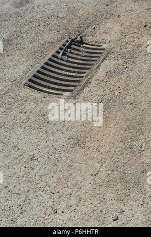 Drainage grille on a country lane. Metaphor 'down the drain'. - Stock Image