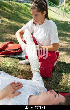 First aid treatment of injured patient, bandaging arm by young female. - Stock Image