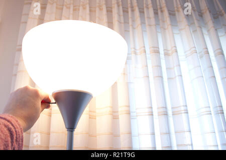 Hand turns the switch on a lamp - Stock Image