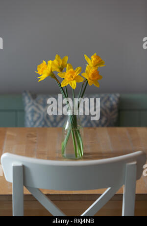 Daffodils in vase on a wooden table with grey background - Stock Image