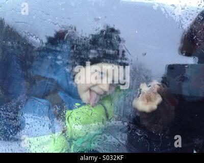 Child portrait over wet window in rainy day - Stock Image