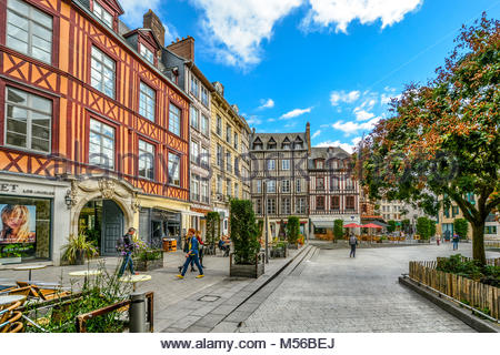 Timber frame homes line a town square in the medieval city of Rouen France with shops, a sidewalk cafe and tourists - Stock Image