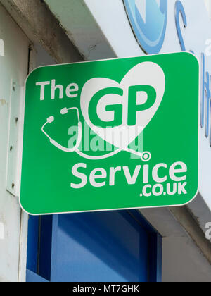 A Green sign on a High Street Pharmacy showing The GP service.co.uk - Stock Image