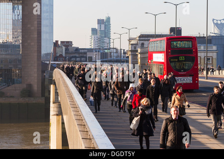 Early morning commuters cross London Bridge for the city on a cold sunny Winter morning - Stock Image