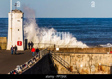 Northumberland, UK. 24th September, 2018. Waves breach the harbour wall on a  warm, partly sunny afternoon at Seahouses, Northumberland, UK. Credit: © NBSN / Alamy Live News - Stock Image