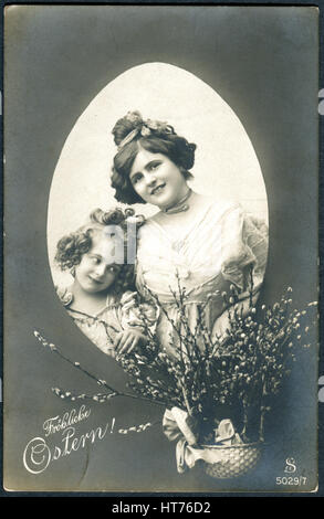 A postcard printed in Germany, shows a mother and daughter and a basket with willow branches. The inscription in - Stock Image