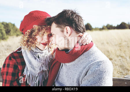 Romantic young couple of lovers look at each other in love sitting in a outdoor wooden bench with nature as background - Stock Image