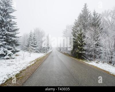 Sparse snow in countryside with empty asphalt road in center centered - Stock Image